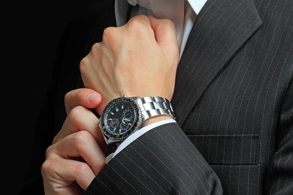 Mand tager et armbåndsur på
