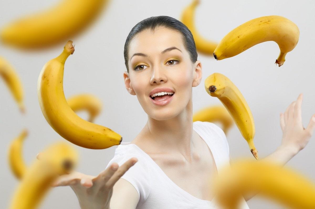 Smuk kvinde omgivet af bananer