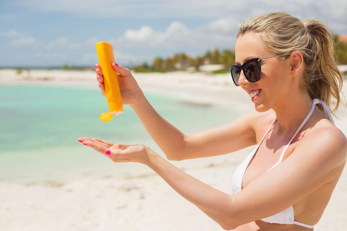 Kvinde i solen med solcreme