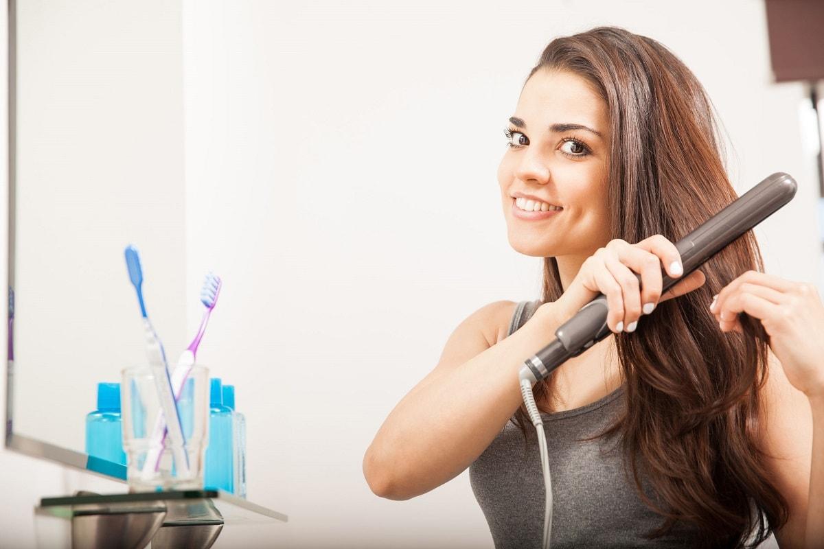 Kvinde med langt hår bruger glattejern